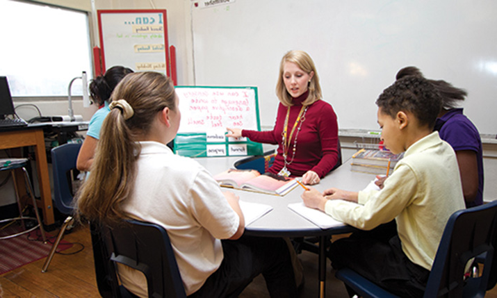 Teacher teaching students at table