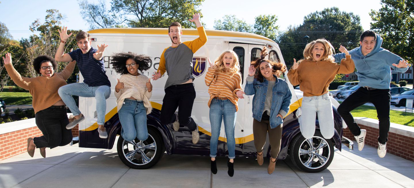 Students jumping in front of the Lipscomb car
