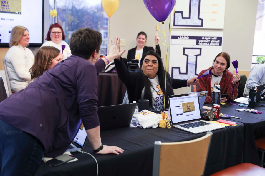 Lipscomb day of giving, people high five behind a lap top to celebrate