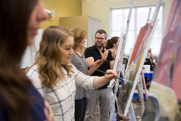 A professor stands with a student in a classroom studio and gives her advice for her painting