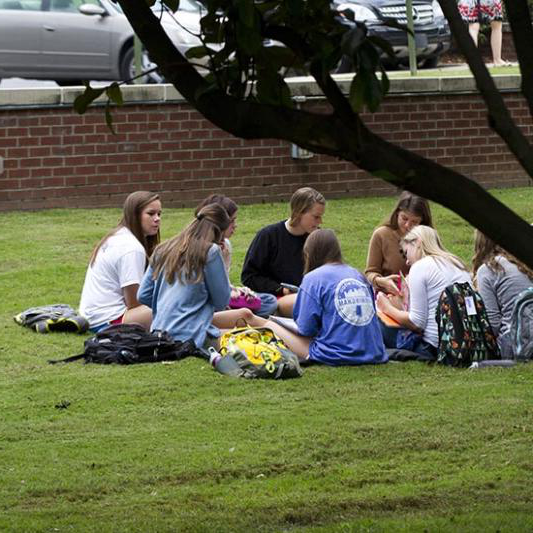 Students sit outside in the grass during a Breakout 教堂 session