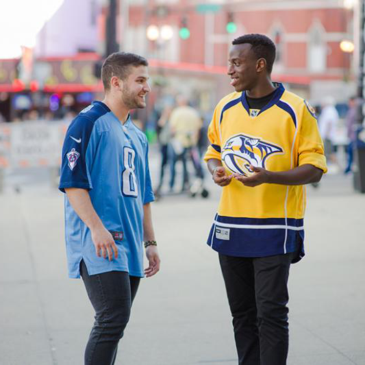 A student in a 纳什维尔 Predators hockey jersey talks with another in a Tennessee Titans football jersey.