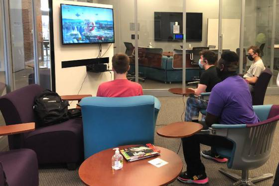 Students sitting in gaming cave playing video games.